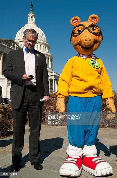 From left Rep Earl Blumenauer DOre checks his phone as Arthur the aardvark from PBS Kids looks on during a news conference to announce efforts to...