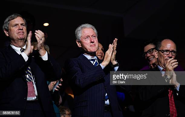 From left Secretary of Agriculture Tom Vilsack former President Bill Clinton and Labor Secretary Tom Perez clap as Vice President Joe Biden speaks at...