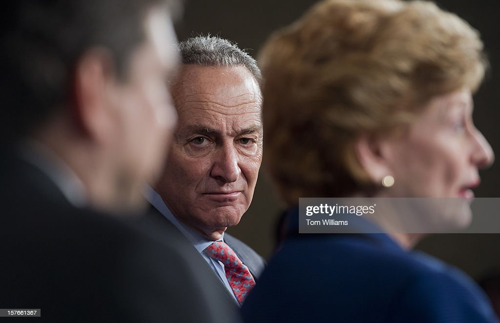 From left, Sens. Mark Begich, D-Alaska, Chuck Schumer, D-N.Y., and Debbie Stabenow, D-Mich., attend a news conference in the Capitol calling on the House to act on a Senate passed tax cut bill that would help the middle class.