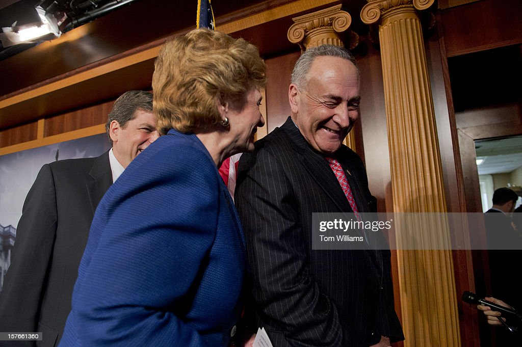 From left, Sens. Mark Begich, D-Alaska, Debbie Stabenow, D-Mich., and Chuck Schumer, D-N.Y., attend a news conference in the Capitol calling on the House to act on a Senate passed tax cut bill that would help the middle class.