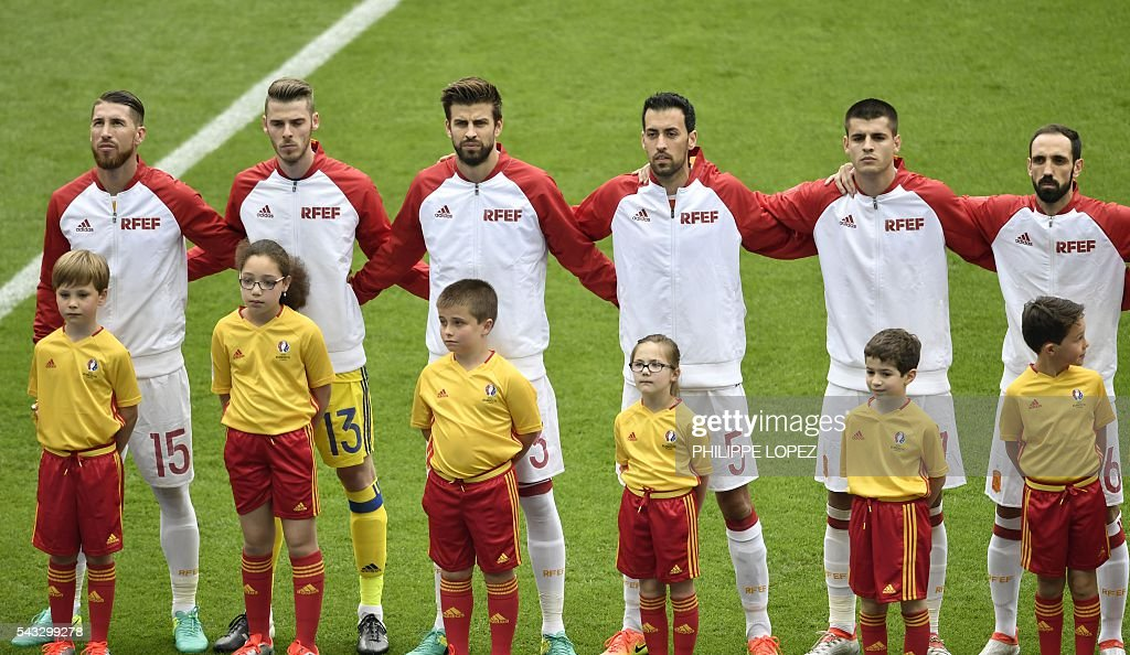 From left, Spain's defender Sergio Ramos, Spain's goalkeeper David De Gea, Spain's defender Gerard Pique, Spain's midfielder Sergio Busquets, Spain's forward Alvaro Morata and Spain's defender Juanfran listen to the national anthem ahead of the Euro 2016 round of 16 football match between Italy and Spain at the Stade de France stadium in Saint-Denis, near Paris, on June 27, 2016. / AFP / PHILIPPE