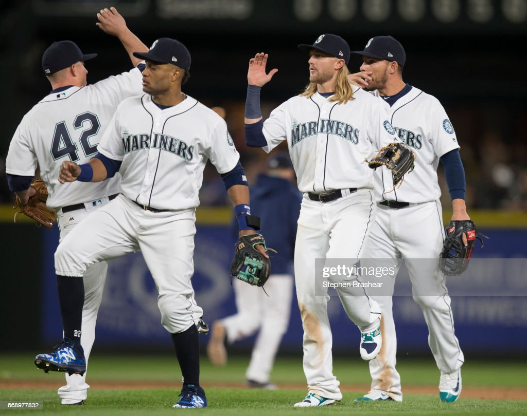 From left, third baseman Kyle Seager #15 of the Seattle Mariners, second baseman Robinson Cano #22 of the Seattle Mariners, shortstop Taylor Motter #21 of the Seattle Mariners and first baseman Danny Valencia #26 of the Seattle Mariners celebrate a victory over the Texas Rangers in a game at Safeco Field on April 15, 2017 in Seattle, Washington. The Mariners won the game 5-0. All players are wearing #42 in honor of Jackie Robinson Day.