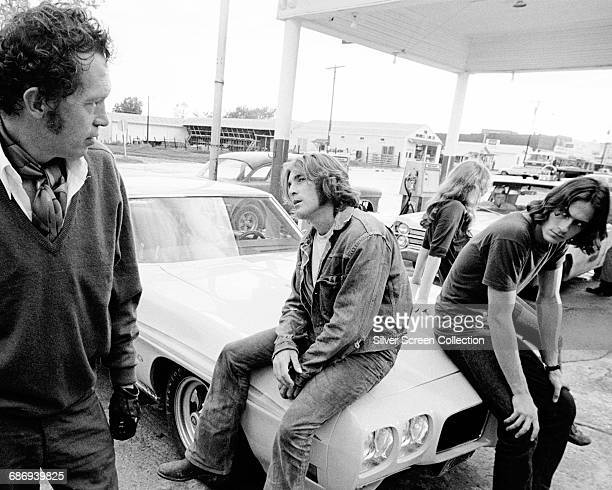 From left to right actor Warren Oates as GTO singersongwriter James Taylor as The Driver actress Laurie Bird as The Girl and Beach Boys drummer...