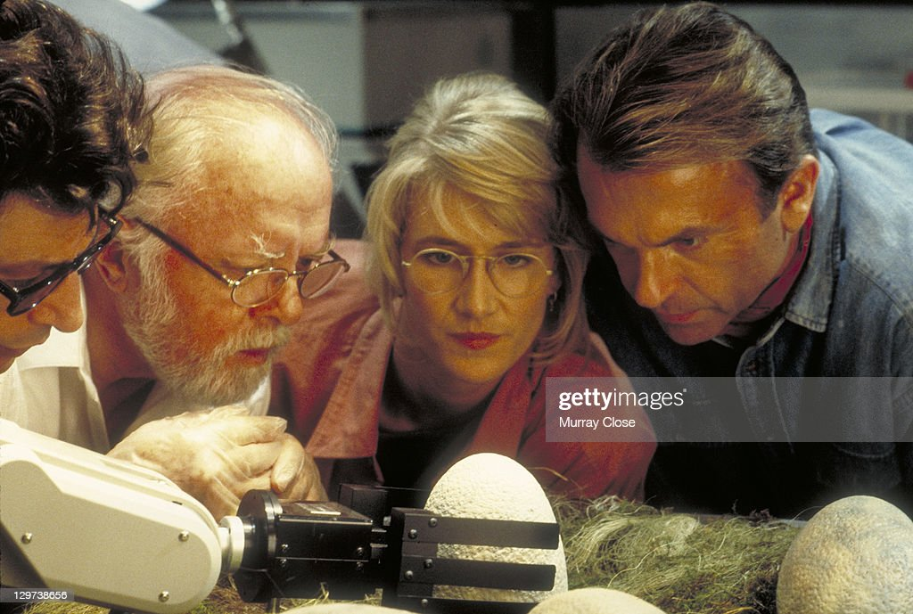 From left to right, actors Jeff Goldblum as Dr. Ian Malcolm, Richard Attenborough as John Hammond, Laura Dern as Dr. Ellie Sattler and Sam Neill as Dr. Alan Grant, watching a robotic arm handle the dinosaur eggs in a scene from the film 'Jurassic Park', 1993.