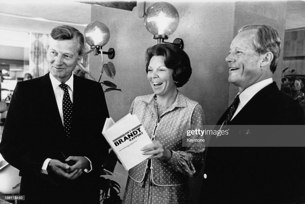 From left to right, Dutch politician Jan de Koning (1926 - 1994), the Minister for Development Cooperation, Queen <a gi-track='captionPersonalityLinkClicked' href=/galleries/search?phrase=Beatrix+of+the+Netherlands&family=editorial&specificpeople=92396 ng-click='$event.stopPropagation()'>Beatrix of the Netherlands</a> and German statesman <a gi-track='captionPersonalityLinkClicked' href=/galleries/search?phrase=Willy+Brandt&family=editorial&specificpeople=94253 ng-click='$event.stopPropagation()'>Willy Brandt</a> (1913 - 1992) with a copy of The Brandt Report in The Hague, Netherlands, 19th May 1980. The report was written by Brandt to review international development issues.