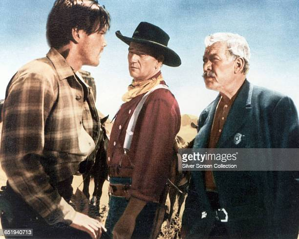 From left to right Jeffrey Hunter as Martin Pawley John Wayne as Ethan Edwards and Ward Bond as Rev Capt Samuel Johnston Clayton in 'The Searchers'...