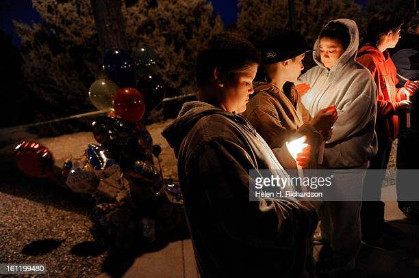 Jose Silva Diego Robles his mother Tanya Robles and daugter Rebecca Robles hold candles during a candlelight vigil for the Long family Neighbors and...