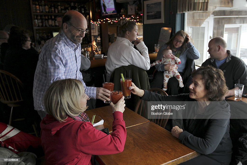 Ken and Joan Silbergleit of New York toast the storm with Joan's sister Nancy Rooks, at right; at the Barnacle Bar and Restaurant. The bar which is on the waterfront, is a local favorite hang-out during storms. The Silbergleits drove up from NY to take in the storm.