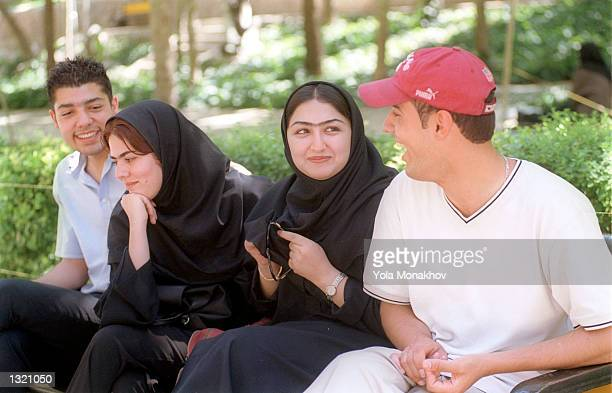 From left to right Peyman Abrahami Hengameh Malekshahey and Shadee Rezayee and Amir Safoverdi sit on a bench in Saie Park June 10 2001 in Tehran on...
