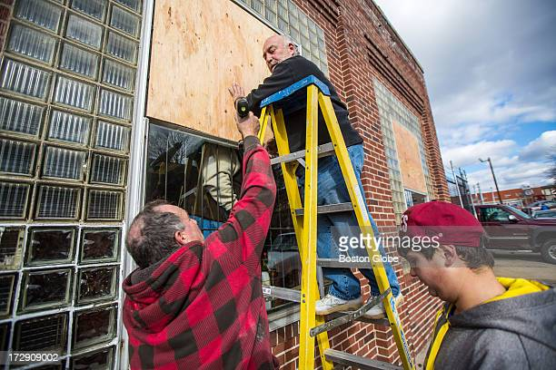 From left to right Ron Hood owner Rene Young and Anthony Mineo boarded up broken windows at AA Automotive on Winter Street after a natural gas...