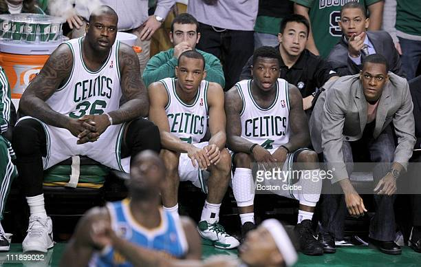 From left to right Shaquille O'Neal Avery Bradley Nate Robinson and Rajon Rondo sit on the Boston Celtics bench watching as a key free throw goes in...