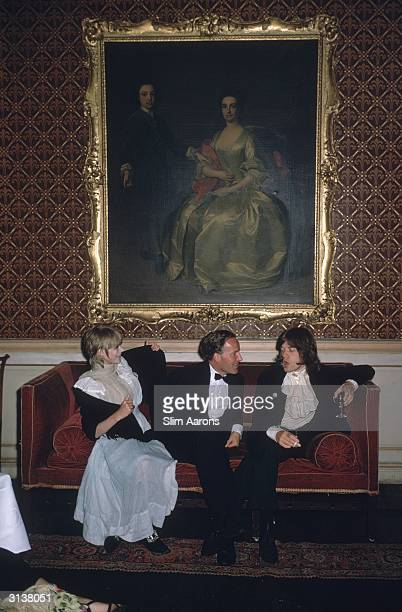 From left to right singer Marianne Faithfull the Honorable Desmond Guinness and Mick Jagger sit on a sofa under a large gilt framed painting of a...