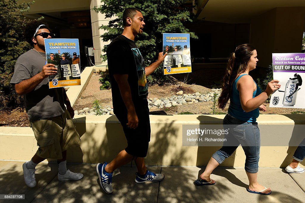 From left to right Tevin Johnson, left, Billy Richardson, middle and Courtney Gallegos, who came out to support Courtney's mother Cindy, a Teamster, hold signs as they walk to protest Molson Coors' annual shareholder meeting outside at 1881 Curtis street in Denver, Colorado on May 25, 2016 in Denver, Colorado. The protestors wanted to raise concerns about the planned closure of the award-winning MillerCoors brewery in Eden, N.C. The closure will impact 450 Teamster families in that state. The decision to close Eden was announced on September 14, just two days before the merger talks between SABMiller (LON: SAB) and AB/Inbev (NYSE: BUD) were formally disclosed to the public. Teamsters will warn shareholders of the likely anticompetitive effects of that decision and how it may be viewed by regulators.