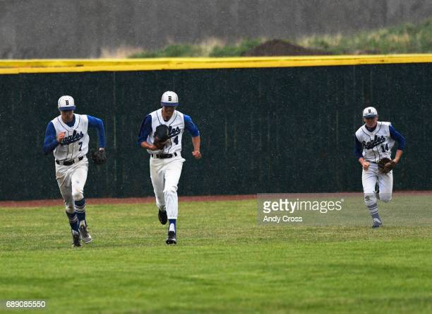 From left to right the Broomfield Eagles outfielders Josh Cox left Mitch Morales center and Hayden Va nDe Pol right come off the field when play was...