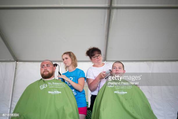 From left Westbrook police officers Kipp Bleicken and Garrett McCarthy get their heads shaved by Jenna MacLean left and Ginny Ayers Law enforcement...