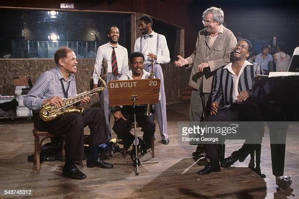 American jazz saxophonist Dexter Gordon (L), American jazz composer and saxophonist Wayne Shorter, unknown, double bass player Ron Carter (center right), French director Bertrand Tavernier and American jazz pianist and composer Herbie Hancock on the set of 'Round Midnight' (Autour de minuit), based on the David Rayfiel screenplay, directed by Bertrand Tavernier.
