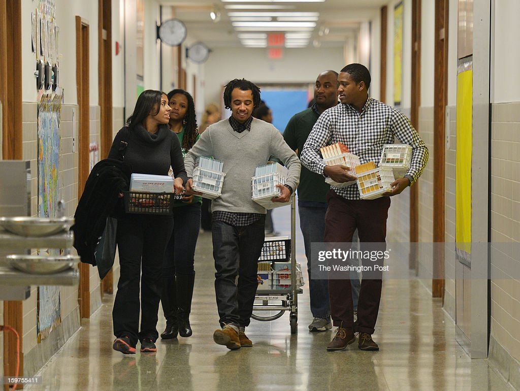 From L-R, Simone Anderson, Britney Whaley, Andre Anderson Thompson, Pat Collier and Justin Knight transport books from storage to be inscribed and gift-wrapped for needy DCPS (DC Public School) children as part of the National Day of Service at Turner Elementary School on Saturday, January 19, 2012, in Washington, DC.