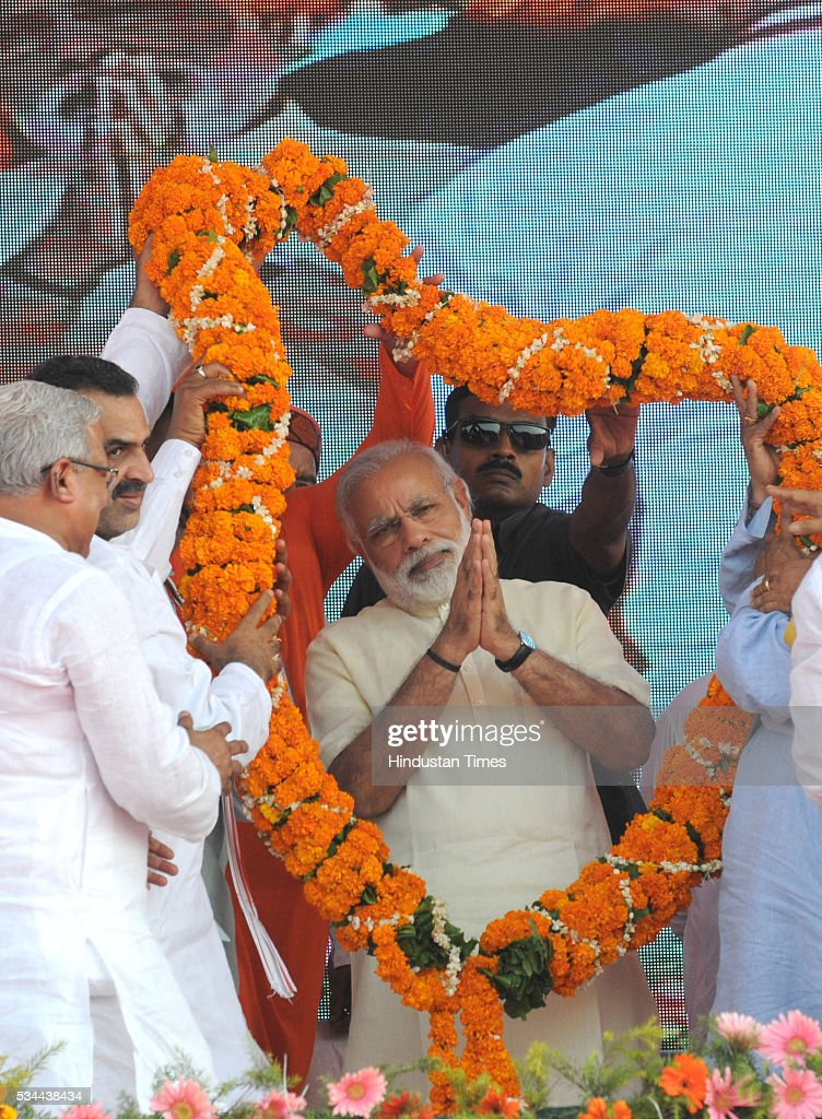 BJP MP from Muzaffarnagar Sanjeev Balyan garlanding Prime Minister Narendra Modi at a rally to mark the second anniversary of the formation of his government at the centre, on May 26, 2016 in Saharanpur, India. Prime Minister Narendra Modi's speech to mark two years of his government focused on farmers and the poor at a massive rally in Saharanpur in Uttar Pradesh, where crucial assembly elections will be held early next year.