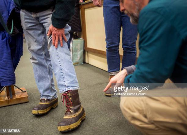 From right Tim Richter a customer service representative takes a closer look at Norris Davis' 24yearold LL Bean boots at the flagship store Davis...