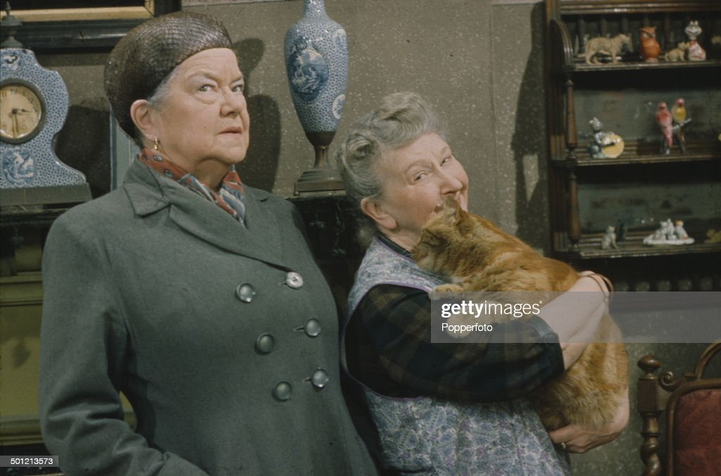 From right to left - English actresses Margot Bryant (1897-1988) as 'Minnie Caldwell' holding a pet cat and Violet Carson as 'Ena Sharples' pictured together in a scene from the television soap opera 'Coronation Street' in 1967.