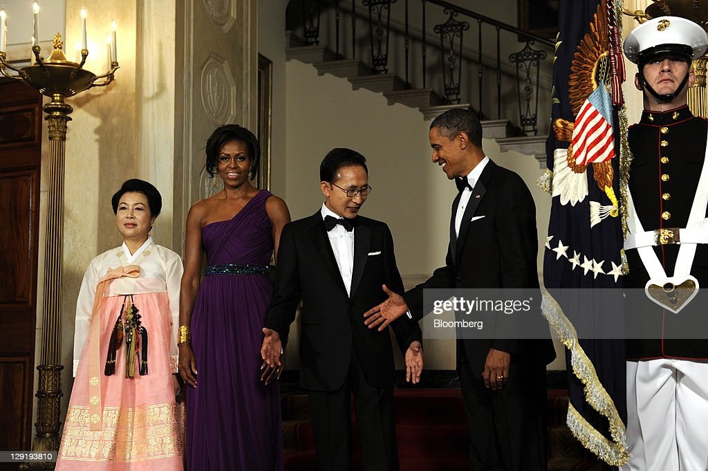 From second right, U.S. President <a gi-track='captionPersonalityLinkClicked' href=/galleries/search?phrase=Barack+Obama&family=editorial&specificpeople=203260 ng-click='$event.stopPropagation()'>Barack Obama</a> extends his hand to Lee Myung-bak, president of South Korea, as U.S. First Lady <a gi-track='captionPersonalityLinkClicked' href=/galleries/search?phrase=Michelle+Obama&family=editorial&specificpeople=2528864 ng-click='$event.stopPropagation()'>Michelle Obama</a> and Kim Yoon-ok, First Lady of South Korea, look on in the Cross Hall of the White House before a state dinner in Washington, D.C., U.S., on Thursday, Oct. 13, 2011. Obama said the U.S. has an 'unbreakable' alliance with South Korea as he welcomed the Asian nation's president for a state visit. Photographer: Roger L. Wollenberg/Pool via Bloomberg via Getty Images