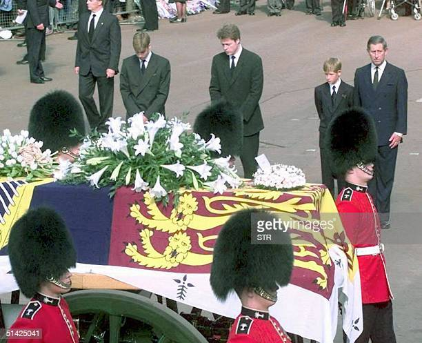 From the left Prince William Earl Spencer Prince Harry and Prince Charles approach the gun carriage with the coffin of Diana Princess of Wales in...