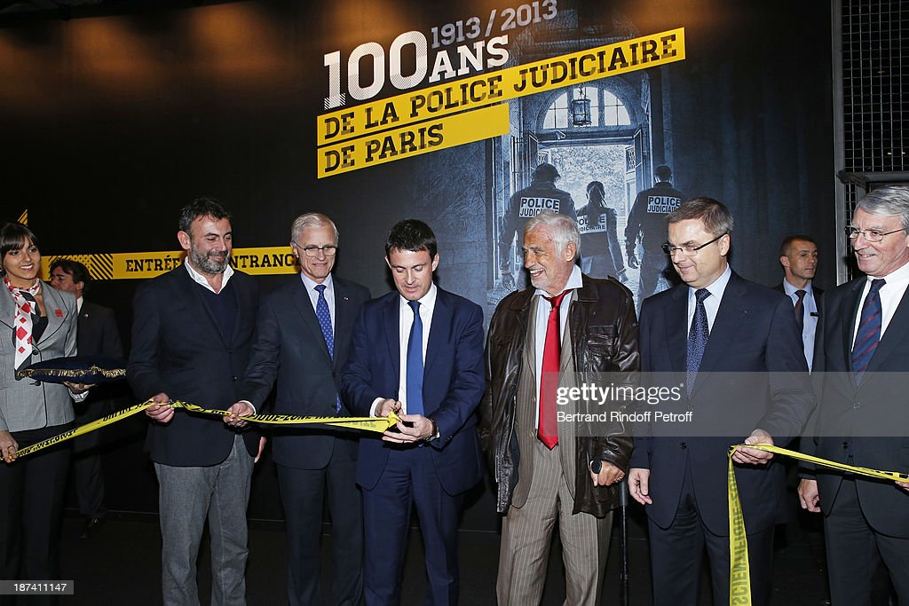 From third left, Paris Prefect Bernard Boucault, French Interior Minister <a gi-track='captionPersonalityLinkClicked' href=/galleries/search?phrase=Manuel+Valls&family=editorial&specificpeople=2178864 ng-click='$event.stopPropagation()'>Manuel Valls</a>, cutting the opening ribbon, legendary actor <a gi-track='captionPersonalityLinkClicked' href=/galleries/search?phrase=Jean-Paul+Belmondo&family=editorial&specificpeople=207029 ng-click='$event.stopPropagation()'>Jean-Paul Belmondo</a> and head of the Paris Judicial Police Christian Flaesch attend the '100th Anniversary Of The Paris Judiciary Police' exhibition opening on November 8, 2013 in Paris, France.
