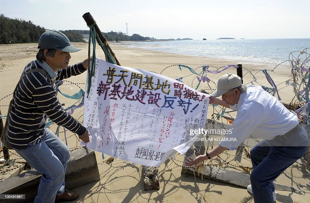 'Japan PM's coalition strained by US base deal ': (FILEs) Anti-US base activists from Shizuoka prefecture put a banner onto the barbed wire and a blockade dividing the US Marine Corps facilities of Camp Schwab from the rest of the city of Nago in the Okinawa prefecture on April 25, 2010. Japan's Premier Yukio Hatoyama faced a fresh political headache when a left-leaning coalition partner attacked his plan to allow for a US airbase to be relocated within Okinawa island.