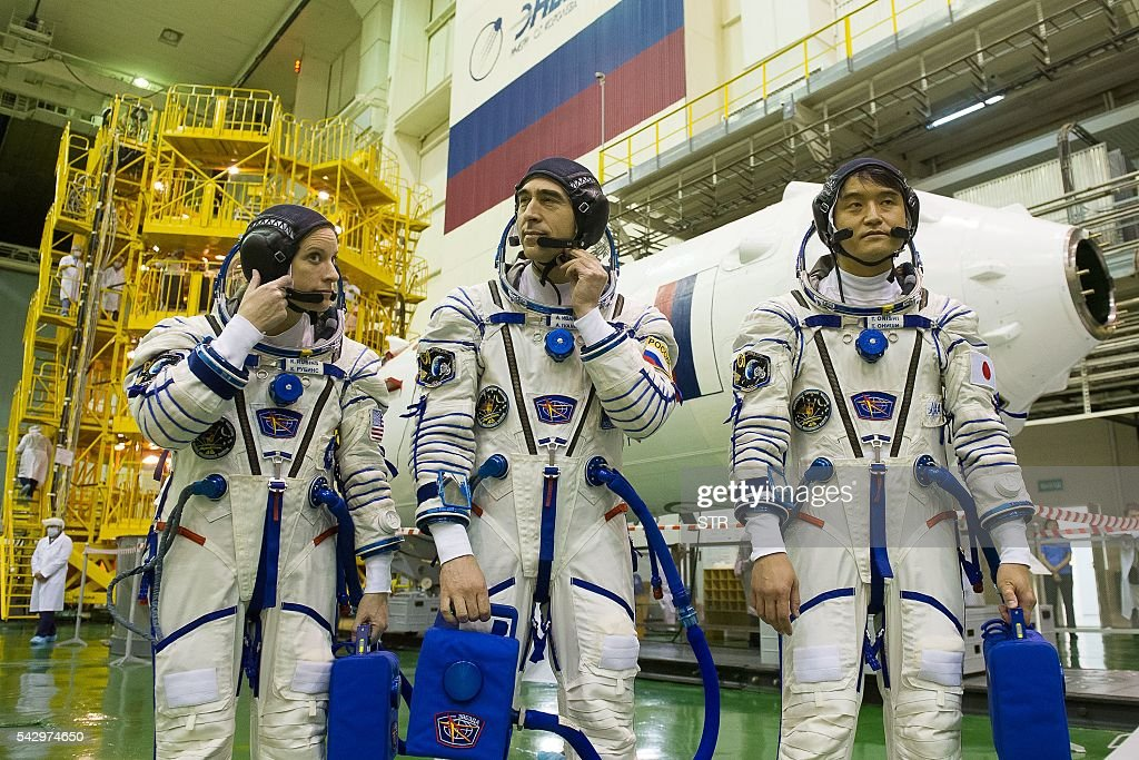 Members of the main crew of the 48/49 expedition to the International Space Station (ISS), US NASA astronaut Kate Rubins, Russian cosmonaut Anatoli Ivanishin and Japanese JAXA astronaut Takuya Onishi walk beside the Soyuz MS01 space vehicle in an assembling department at the Russian-leased Baikonur cosmodrome in Kazakhstan on June 25, 2016. The trio is to take off from Kazakhstan's Baikonur cosmodrome to the International Space Station (ISS) on July 7, 2016. / AFP / STR