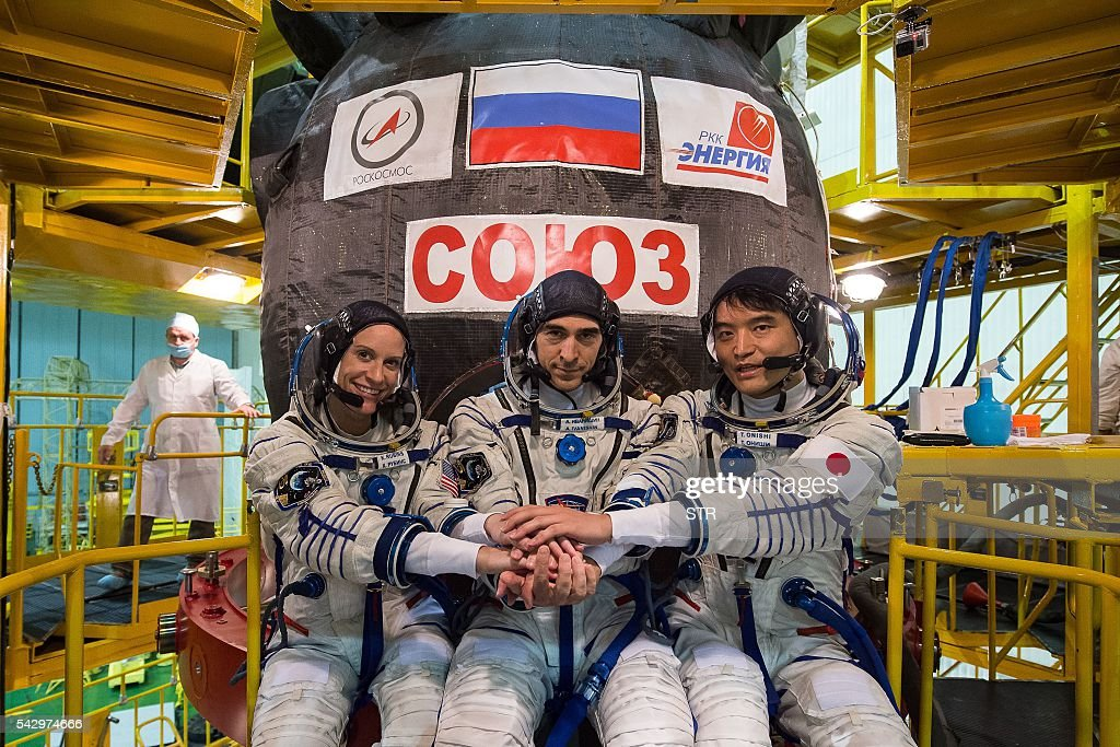 Members of the main crew of the 48/49 expedition to the International Space Station (ISS), US NASA astronaut Kate Rubins, Russian cosmonaut Anatoli Ivanishin and Japanese JAXA astronaut Takuya Onishi pose in front of the Soyuz MS01 space vehicle in an assembling department at the Russian-leased Baikonur cosmodrome in Kazakhstan on June 25, 2016. The trio is to take off from Kazakhstan's Baikonur cosmodrome to the International Space Station (ISS) on July 7, 2016. / AFP / STR