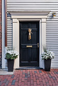 Front black door with two potted flowers