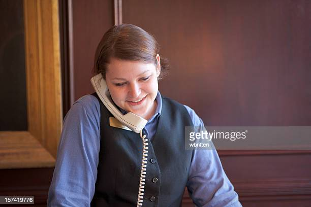 A front desk employer speaking to a guest on the phone