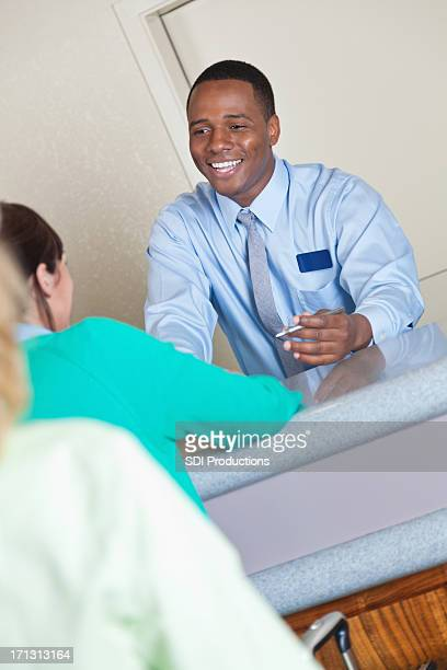 Front desk worker assisting hotel guest