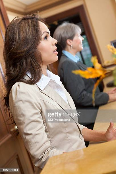 Front desk worker helping guests check in at hotel lobby
