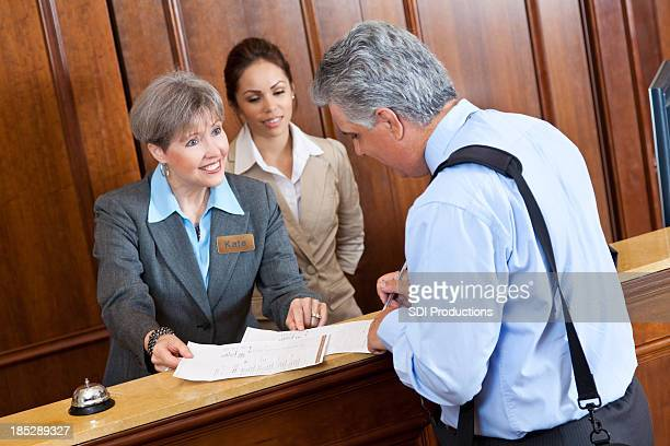 Front desk worker showing hotel bill to guest
