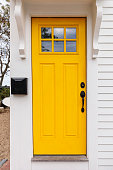 Front door of a beach house with bright yellow color