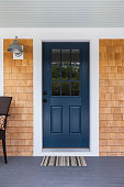 Front dark blue door with white accents and wood siding with a nice porch light and a comfortable chair and a welcoming doormat