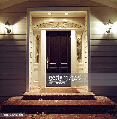 Front door of house with lights at night : Stock Photo