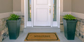 Front door with doormat plants and glass panel. White front door of a house with the word welcome printed on the brown doormat. Ornamental plants and glass panels are on each side of the door.