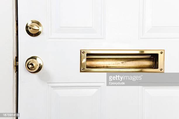 A front door with mail slot, doorknob and deadbolt lock