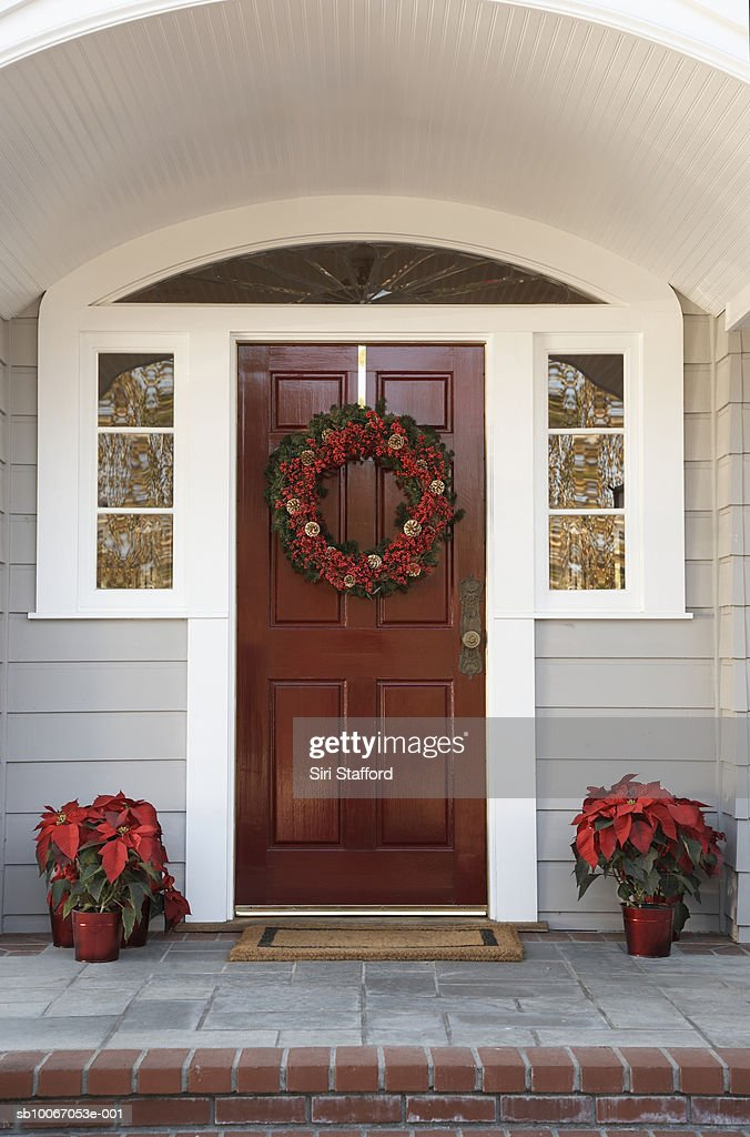 Front door with wreath and poinsettias decoration : Stock Photo