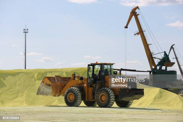 A front end loader moves sulfur for the production of sulfuric acid at the PhosAgroCherepovets fertilizer plant operated by PhosAgro PJSC in...