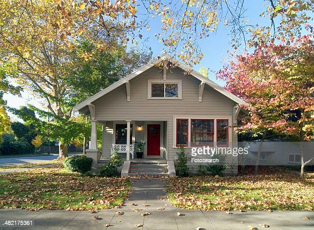 Front exterior of a gray bungalow with red door