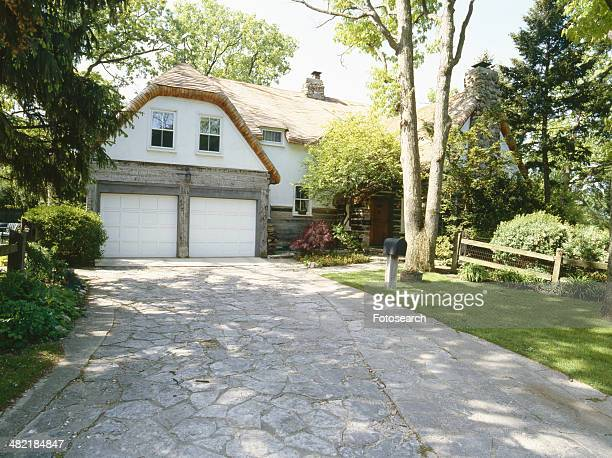 Front exterior of driveway leading to garage of traditional home