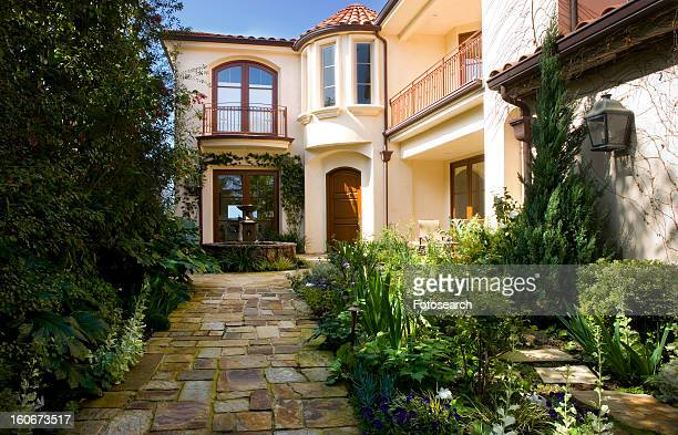 Front exterior of spanish home with fountain