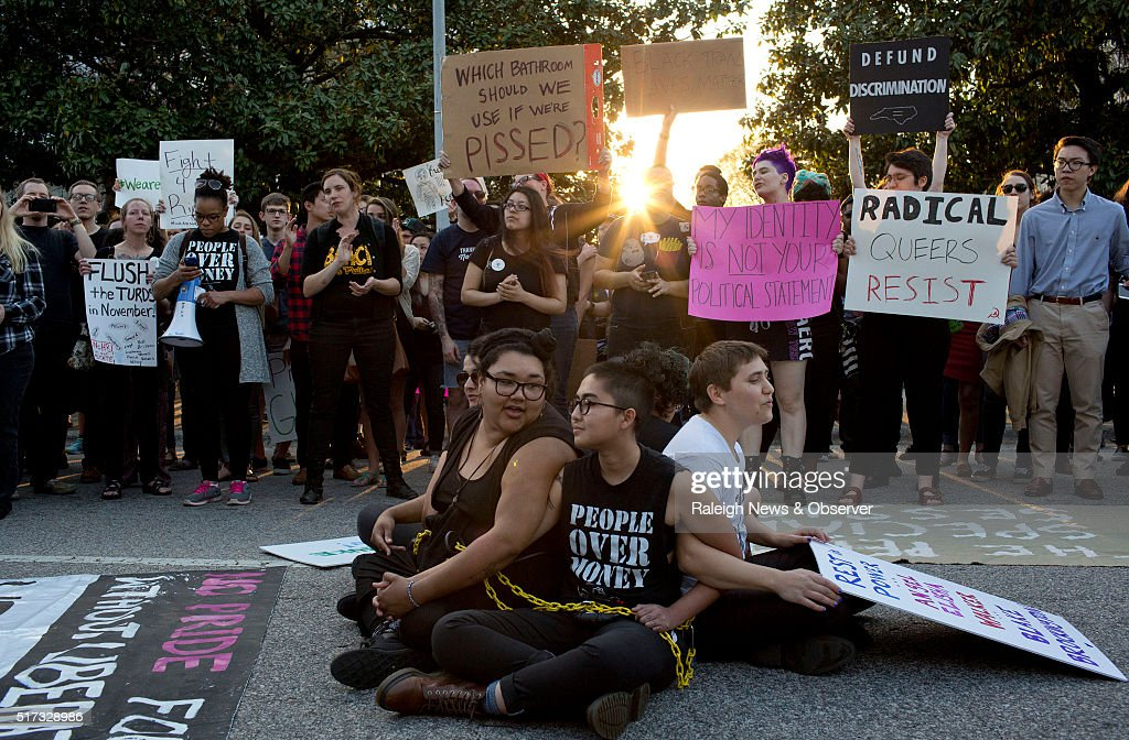 Front from left demonstrators Jess Jude Loan Tran and Noah RubinBlose sit chained together in the middle of the street during a protest against House...