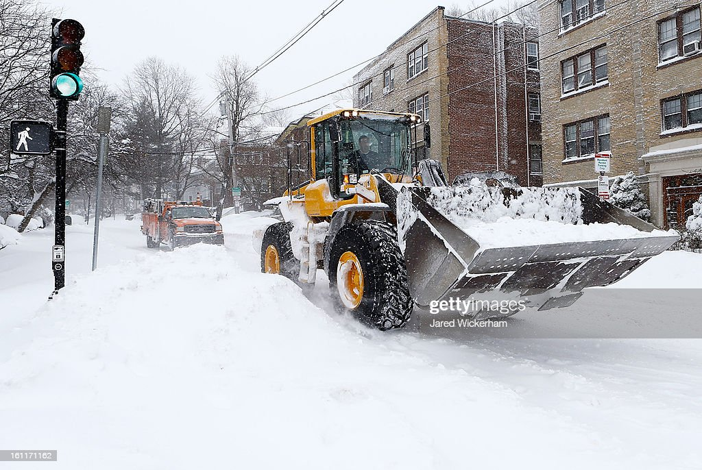 A front loader and truck drives down Warren Street in the Brighton neighborhood on February 9, 2013 in Boston, Massachusetts. The powerful storm has knocked out power to 650,000 and dumped more than two feet of snow in parts of New England.