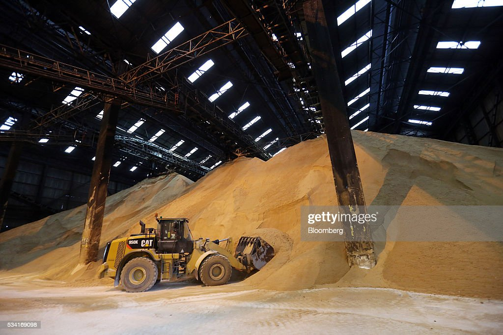 A front loader moves raw cane sugar in the storage warehouse at the Tate & Lyle Plc Thames Refinery, operated by American Sugar Holdings (ASR) Group, in London, U.K., on Wednesday, May 25, 2016. Tate & Lyle will report full year earnings on Thursday, May 26. Photographer: Chris Ratcliffe/Bloomberg via Getty Images