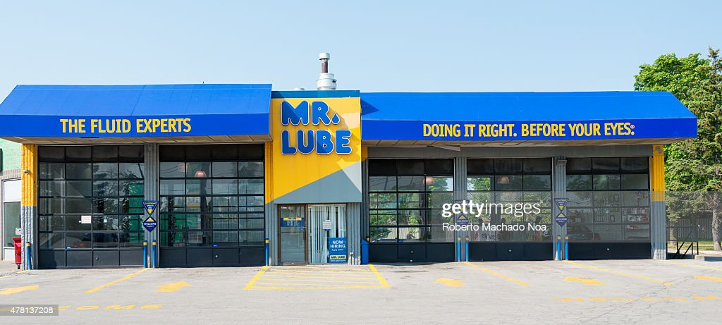 Front of bright blue and yellow Mr. Lube drive thru oil change station with two small car bays and two large bays during the day.