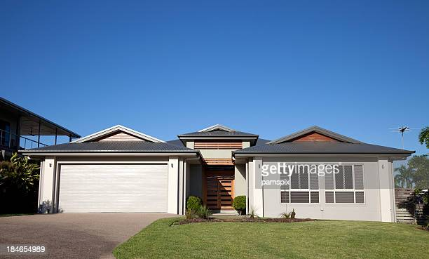 Frente de casa moderna con hierba verde y el azul cielo